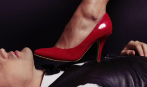 fashion studio photo of impassioned couple. office love story.woman's legs in red classic shoes in man's hands