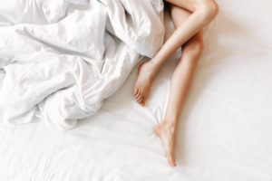 Bare legs on an unmade white bed