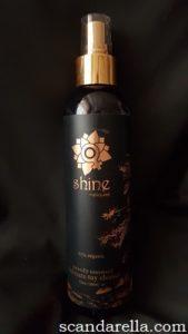 Upright Sliquid Shine black and gold spray bottle on black background