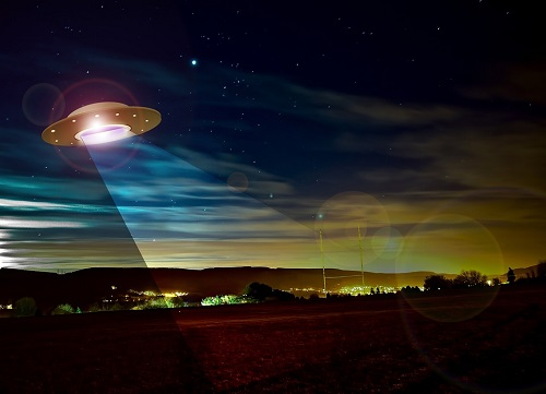 Night sky over a sports field with a cartoonish UFO's spotlight illuminating a wegde of grass