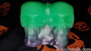 Uberrime Calaveras Halloween Dildo Review, close up of a pair of skull shaped dildo testicles with a silver and black base and a fluorescent green top, on a black background covered in orange skulls