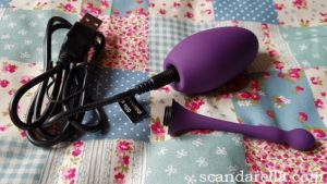 Lovehoney Desire Love Egg Review, image showing a purple silicone love egg with its sensor tail removed and the charging cable attached to the base